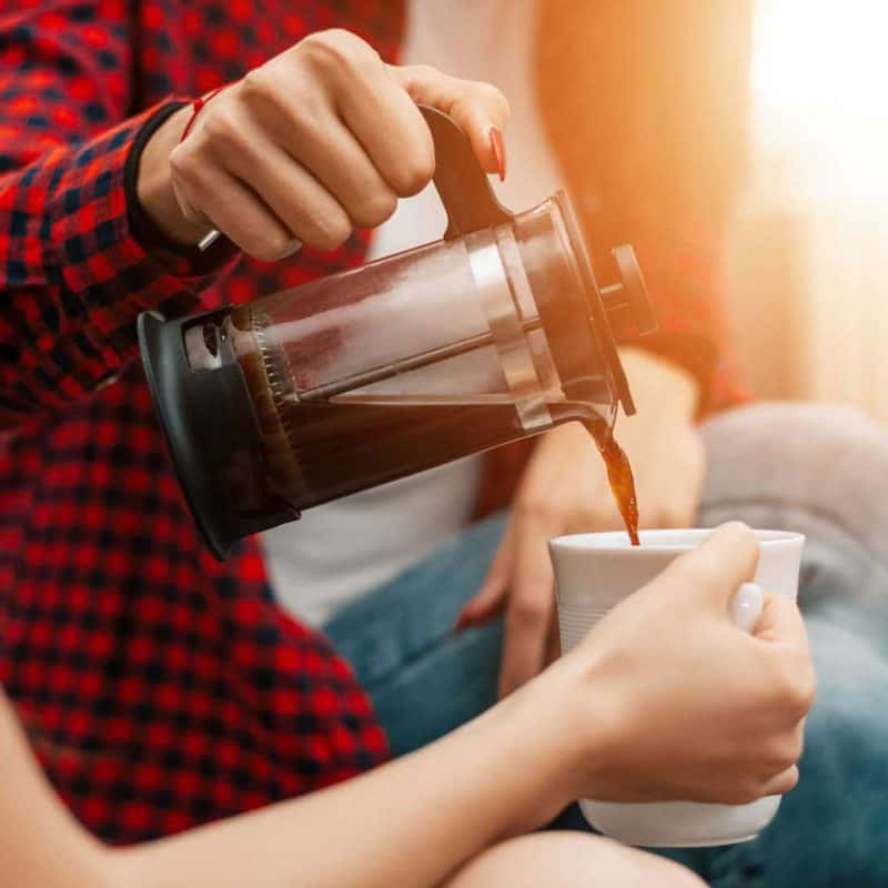 woman pouring french press coffee